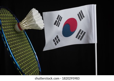 Shuttlecock, badminton racket, and the South Korea flag flutters against the dark background.