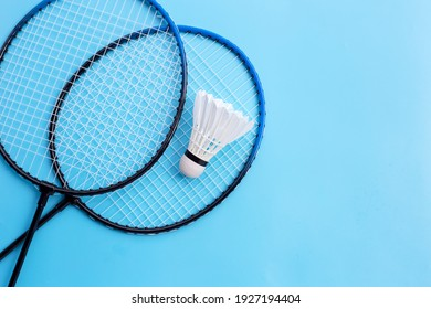 Shuttlecock and badminton rackets on blue background. Copy space