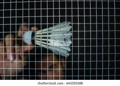 Shuttlecock and net badminton racket in dark background.