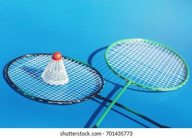 Shuttlecock on badminton racket on blue background. Sport concept