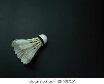 Shuttlecock on a black background, isolated, dark tones, with space message.