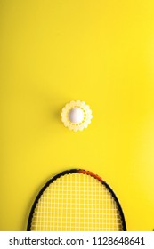 Shuttlecock and racket for playing badminton on a yellow background. Minimalism. Concept summer razlecheny
