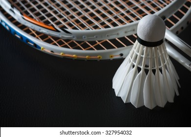 Shuttlecock and rackets on black background
