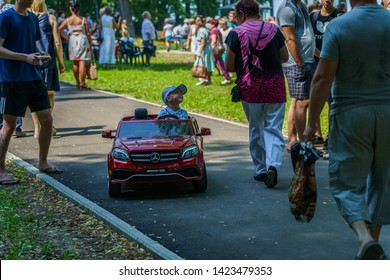 SHUYA, RUSSIA - JUNE 8, 2019: 5 years old boy rides a toy car along a park alley on a summer day