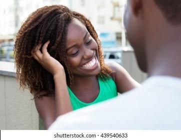 Shy african girl flirting with friend