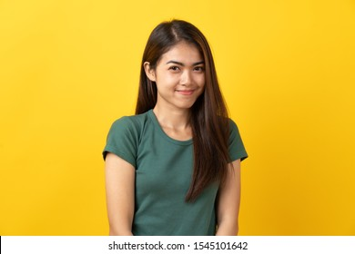 Shy asian young woman smiling facial expression on yellow background.
