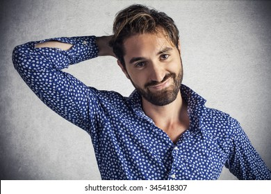 Shy attractive bearded man with hand behind head