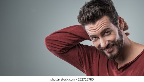 Shy attractive guy smiling at camera with hand behind head