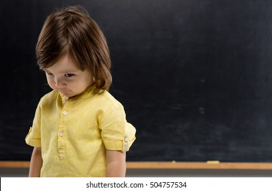 Shy child on blackboard.