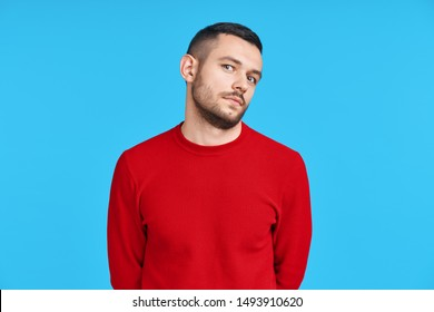Shy confused man portrait on blue background. Emotions concept