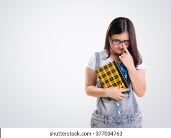 Shy geeky Asian school girl looking to her side with awkward gesture, on white for copy space