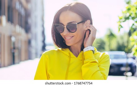 Shy girl. A close-up photo of a beautiful toothy smiling girl in a yellow hoodie and dark sunglasses, with smartwatch on her hand, tucking her and looking aside shyly.