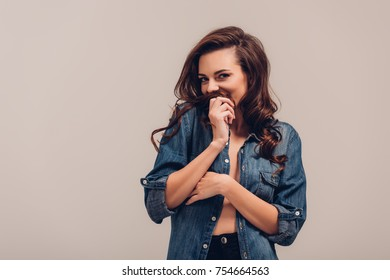 shy girl in denim shirt smiling at camera isolated on grey