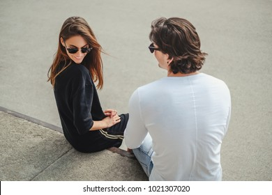 Shy girl sitting on a wall with boyfriend and smiling while he is flirting with her