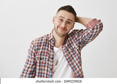 Shy guy tries to ask lovely woman for date. Portrait of happy charming young male with bristle in trendy eyewear holding hand on back of head and smiling, feeling awkward and embarrassed. Copy space