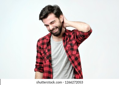 Shy guy tries to ask lovely woman for date. Portrait of happy charming young male with bristle holding hand on back of head and smiling. Feeling awkward and embarrassed.
