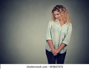 Shy insecure young woman looking down avoiding eye contact standing isolated on gray wall background