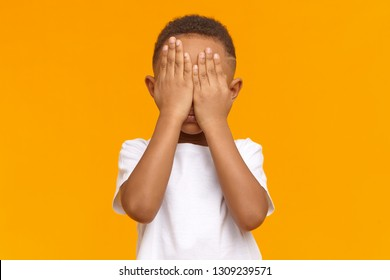 Shy little boy feeling ashamed because of his bad behavior, crying, not showing his tears. Isolated shot of unrecognizable male kid with hands on his face, being afraid of scary movie. Body language