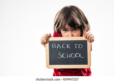 shy little boy hiding behind a writing slate to protect against a scary back to school, white background studio