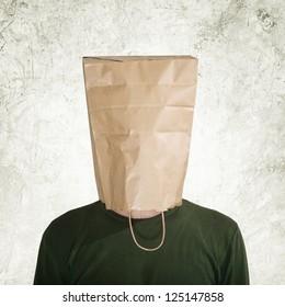 Shy man. Head in the paper bag. Man hidden behind the shopping bag.