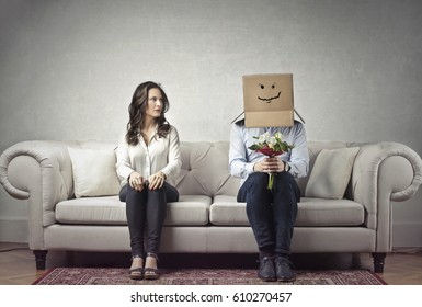 Shy man sitting next to a woman with his head covered by a cardboard box