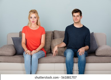 Shy Man Sitting On Couch Flirting With Woman At Home