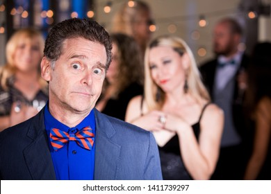 Shy man with woman admirer at a party