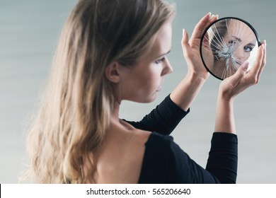 Shy pretty teenage girl with mental problems holding a small mirror
