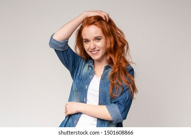 Shy Redhead Girl Touching Hair While Posing On Camera On Light Studio Background, Copy Space