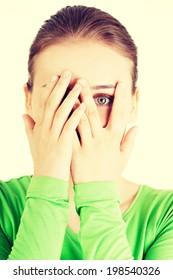 Shy or scared teenage girl peeking through covered face.