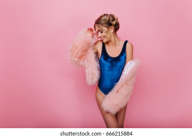 Shy slender girl with blonde hair smiling and posing with hand up, standing on bright background. Adorable young woman in blue bodysuit having fun in pink room and touching her face