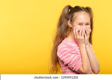 shy smiling embarrassed girl covering mouth with hands. young cute child emotional portrait on yellow background.