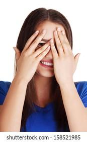 Shy teenage girl peeking through covered face , isolated on white.