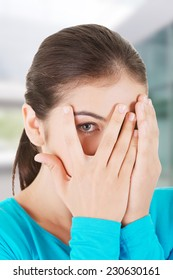 Shy teenage girl peeking through covered face.