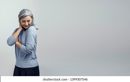 Shy Woman With Grey Hair Poses For The Camera. Beautiful Woman Looks Down And Crosses Her Arms While Touching Hair.