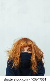 Shy woman hides in her sweater.