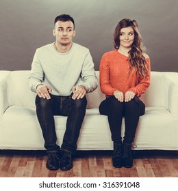 Shy woman and man sitting on sofa couch. First date. Attractive girl and handsome guy meeting dating and trying to talk. Instagram filtered.