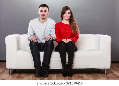 Shy woman and man sitting on sofa couch next to each other. First date. Attractive girl and handsome guy meeting dating and trying to talk.