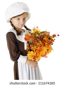 "A shy young elementary ""pilgrim"" with a bouquet of autumn flowers, berries and leaves.  On a white background."