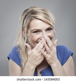 Shy young woman is hiding her laughter behind her hands