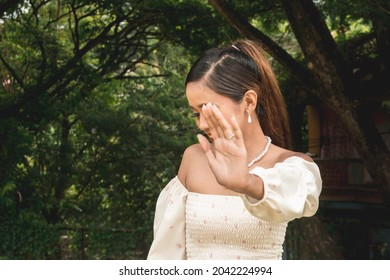 A shy young woman playfully pleads to not have her photo taken while at the park. Self conscious about her image.