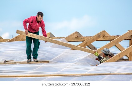 Shymkent Kazakhstan April 11, 2019.The construction of the roof of a residential house. Roofers repair construction contract. The construction team installs carcass and insulation on the roof.