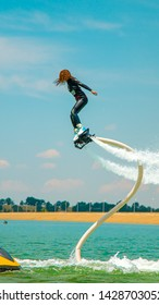 Shymkent, Kazakhstan - June 11, 2019; The girl flies over the water against the sky on a flyboard on a sunny day.