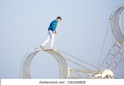 Shymkent Kazakhstan March 23, 2019. Street acrobat stuntman does tricks on a moving wheel. A man moves upwards overcoming fear and obstacles.