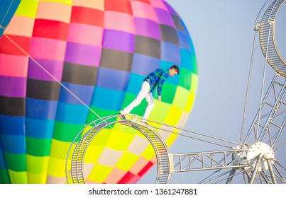 Shymkent Kazakhstan March 23, 2019. Street acrobat stuntman does tricks on a moving wheel. A man moves upwards overcoming fear and obstacles. on the background of balloons