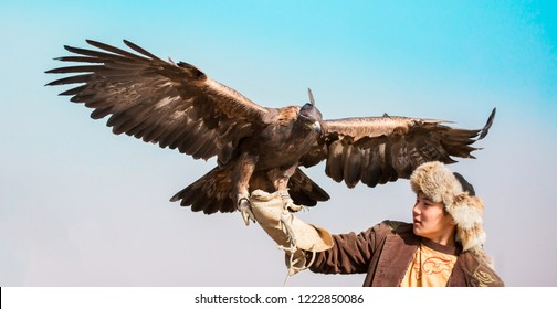 Shymkent, Kazakhstan - October 26, 2018: Kazakh hunter (Berkutchi) with golden eagles on hand. Hunting with the help of an eagle on a hare. Hunter on a horse with a bird in his arms.Kazakhstan tourism