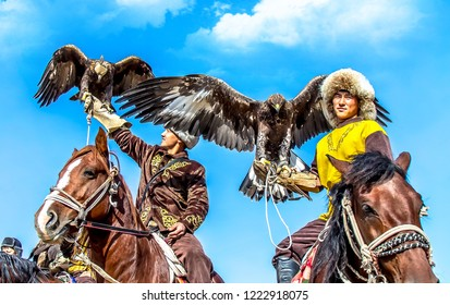 Shymkent, Kazakhstan - October 26, 2018; A holiday in honor of the end of the autumn field work. A hunter rider with a bird of prey on his hand at a holiday on a city beach on a sunny day.