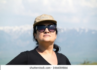 Shymkent, Kazakhstan-May11,2019; Portrait of a woman of 43 years old in the sunglasses of the Asian nation against the sky.