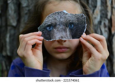 Shyness. Young girl playing with a bear mask.