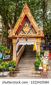 Si Racha, Thailand - March 16, 2019: Red, gold, blue gate on stairway to Wat Koh Loy Buddhist shrines on the hill of Ko Loi Island with gren foliage. Donation box at bottom.